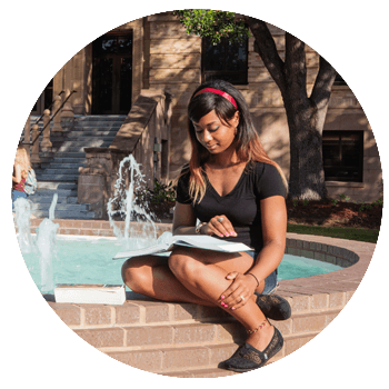 College student studying at the H2O Fountain, near the Chemistry Building